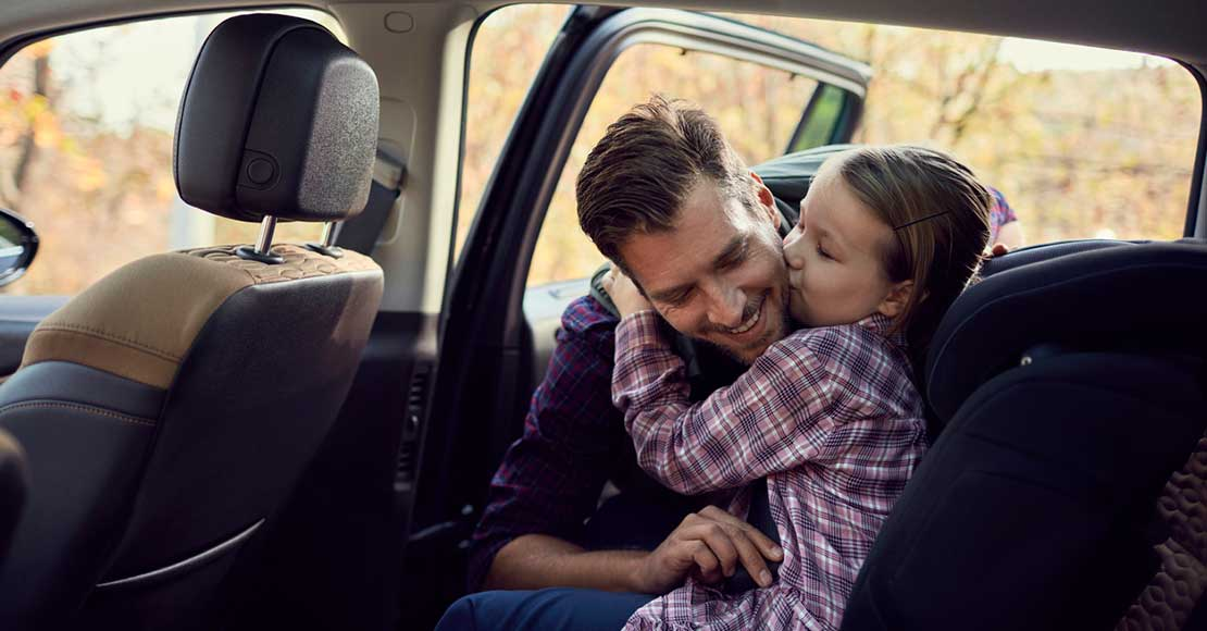 Far fester datter i barnesete i bil
