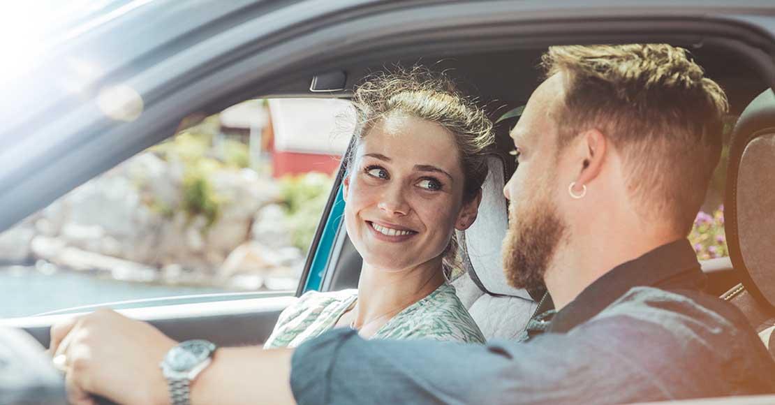 Et par kjører bil i solskinn