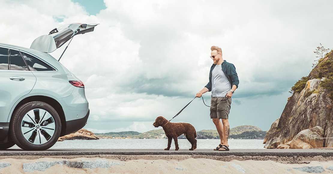 Mann lufter en hund bak en Mercedes-Benz EQC