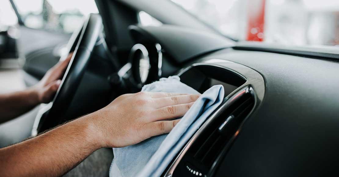 Dashbord i bil vaskes med klut