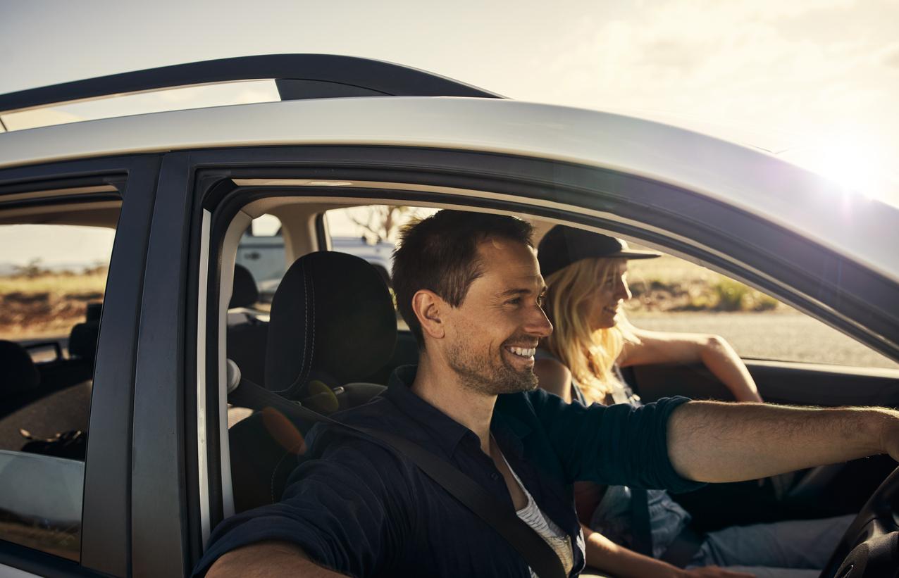 Par som smiler mens de kjører bil i solskinn