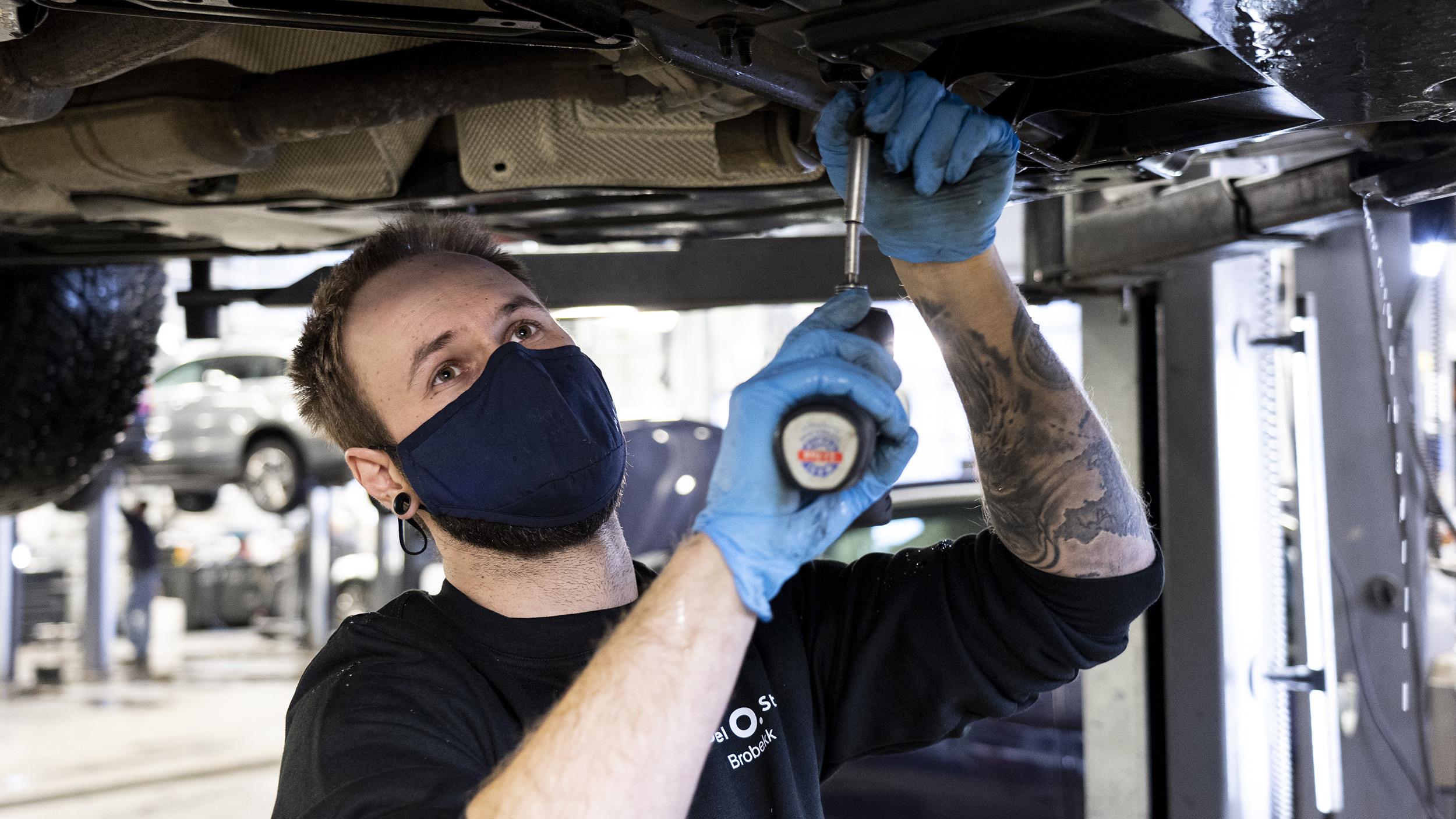 Bilmekaniker arbeider under en bil