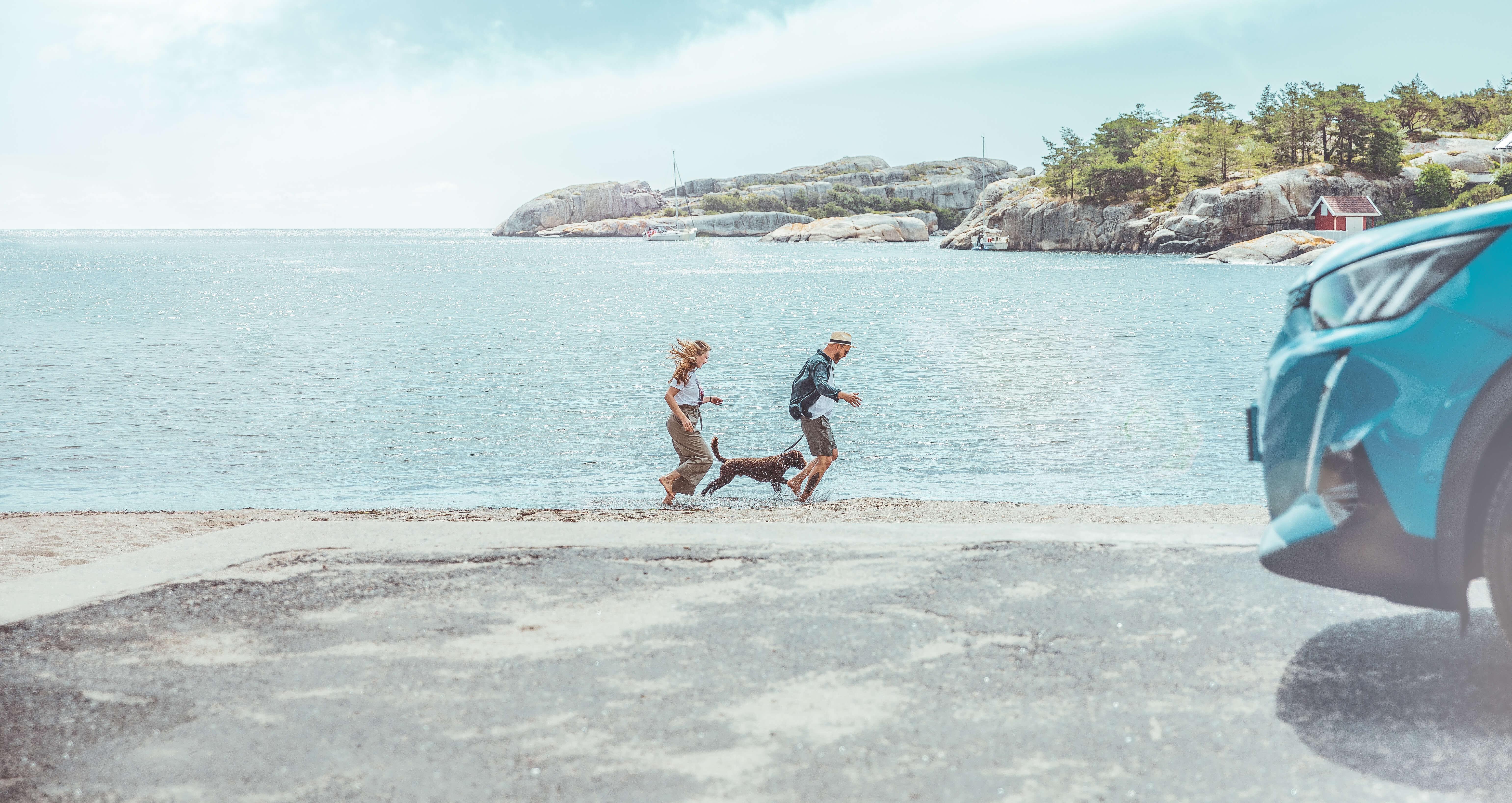 To mennesker og en hund på en strand med bil i forgrunnen