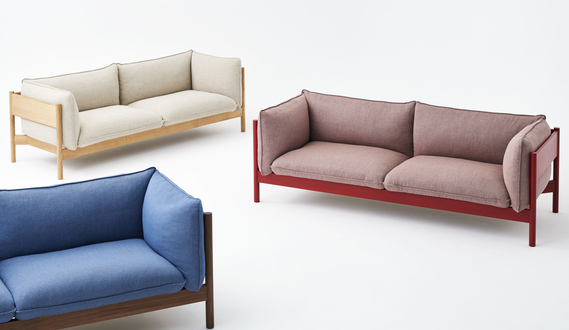 Three sofas displayed randomly. One is yellow, the other one is red, and the last one blue.