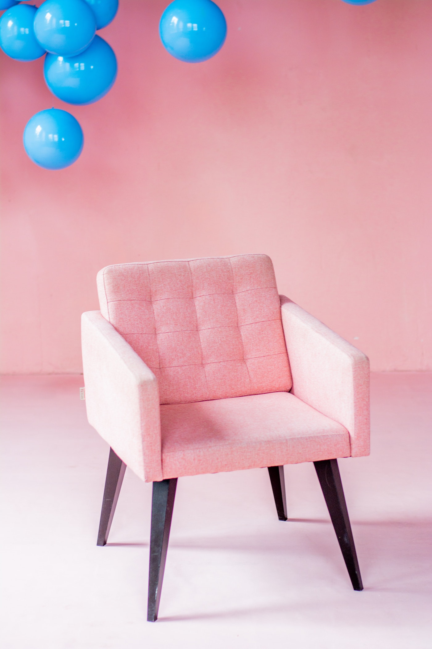A pink lounge chair with blue balloons in background
