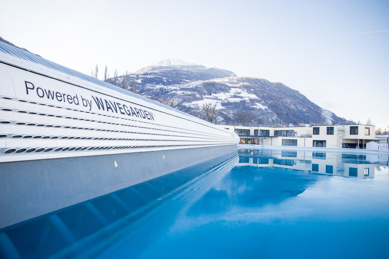 foreground shot of wavepool and Swiss alps in background